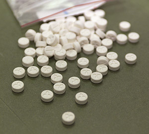 Photo of Ecstasy tablets spilled out onto a table.