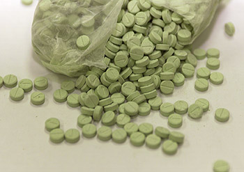 Photo of green Ecstasy tablets spilled out on to a table.